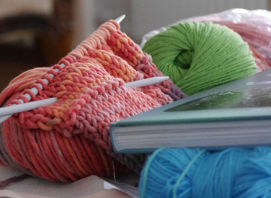 Garnnøgler, strikkepinde og bog