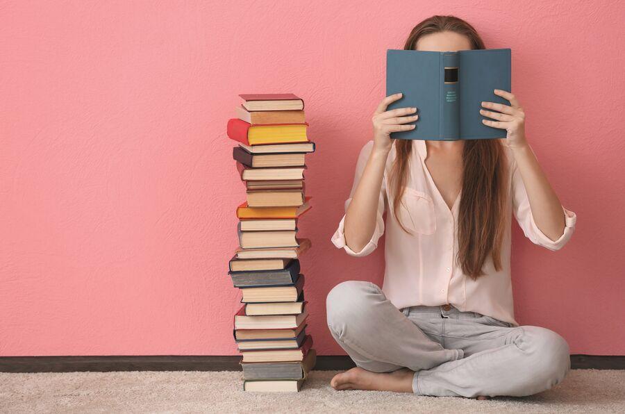 Læsende kvinde ved siden af bogstak