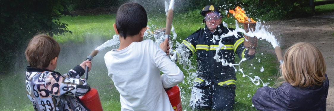 Børn og brandmand leget med vand